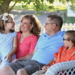Family sits on front porch together