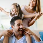Dad, mom and daughter laugh with each other