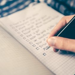 Hand is writing to-do list in a notebook