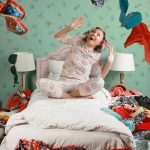 Woman stares at clutter in bedroom
